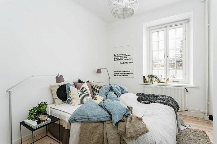 ungemachtes Bett mit vielen farbigen Decken, Holzboden mit ...