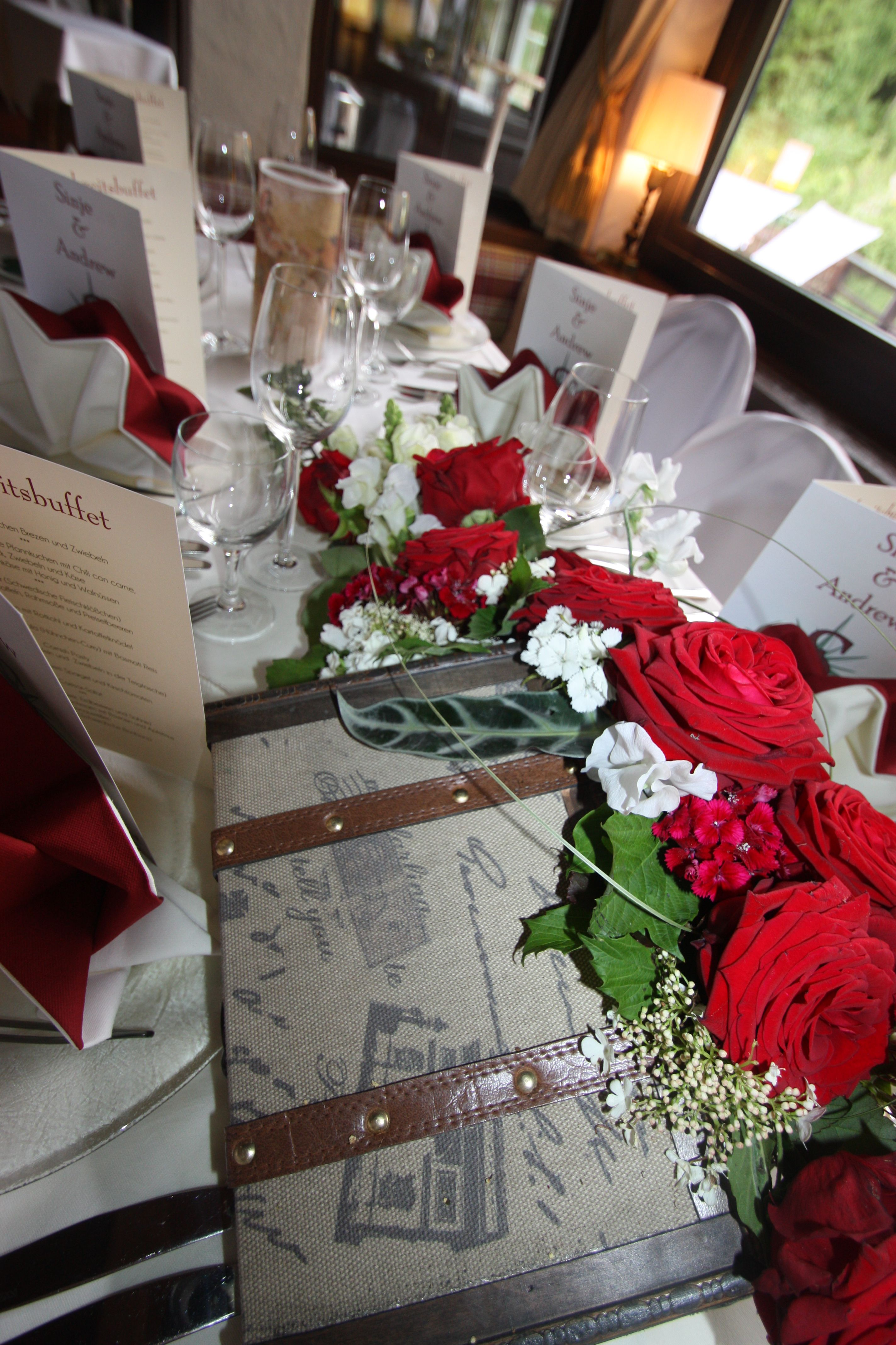 Tischdekoration Mit Roten Rosen Und Efeu In Koffern Hochzeitsmotto