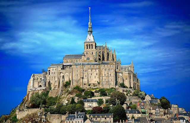 Viewed from the flat stretches of the Normandy shore, the abbey of Mont St. Michel rises over the water like a ghostly apparition. This ancient citadel has been, at various times in its long history, a sacred pilgrimage for those seeking religious salvation, an unconquerable fortress, a prison, and now, a UNESCO World Heritage site. …