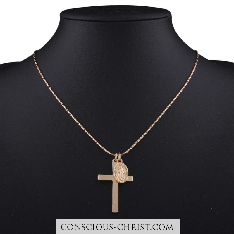 Photo of A filigree rope chain with a duo of pendants. It shows a golden Jesus Christ cro…