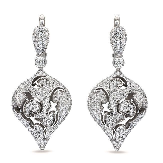 These marvelous dangle earrings feature round-cut pave set diamonds in 18-karat white gold. The beautiful earrings are secured with clip backs and glimmer with a highly polished finish.