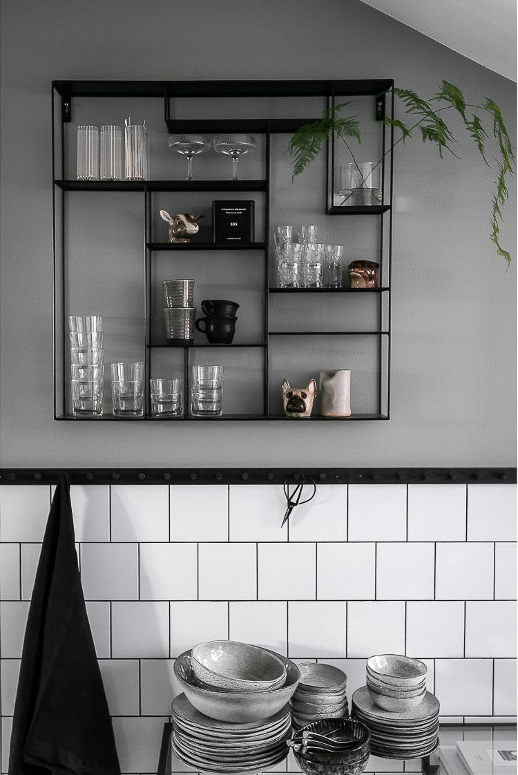 Une cuisine au design noir et un papier-peint fleuri font la
