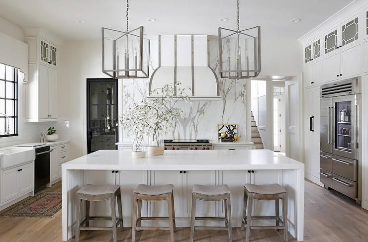 Eye Catching Steel And Glass Lanterns Hang Over A White Center Island Finished With A White Quartz Waterfal White Kitchen Accessories White Kitchen Island Home