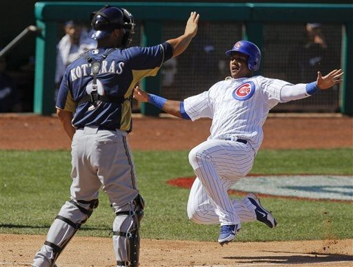 Chicago Cubs' Starlin Castro, right, scores past Milwaukee Brewers catcher George Kottaras on a double by Ian Stewart