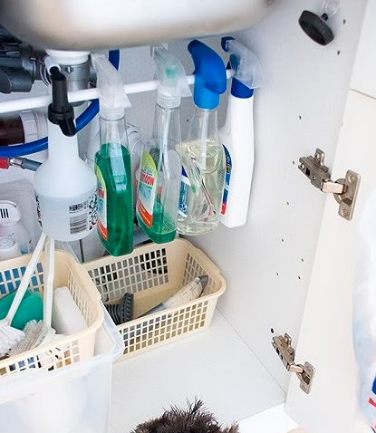 So many renters are starved for space. This is one idea we all should use! An extending bar under the sink to hang those bottles, creating space underneath! describe the image