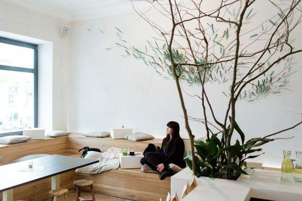 Ambiente clean, com bancos simples de madeira e plantas. No Restaurante Daluma, em Berlim