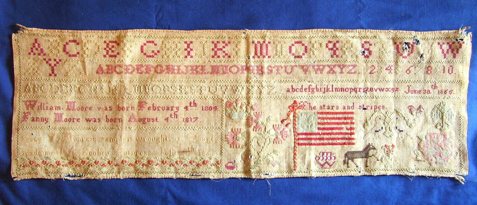 This sampler was made by Lucy V. Moore in 1865 at the Osage Academy. As nearly as I can read from the faded letters, J. A. Scobey was her tutoress and the sampler was done in July. The sampler has her parents' names along with different renderings of the alphabet, numbers, and probably items of interest to Lucy