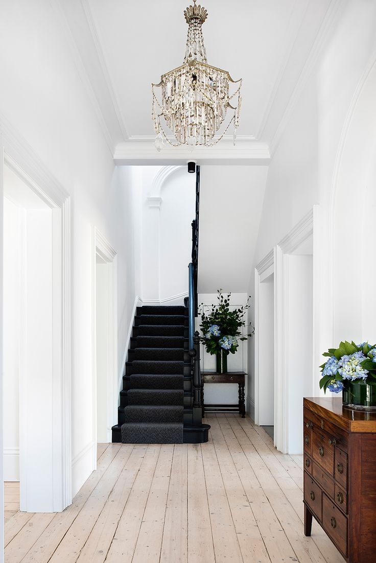 Natural wood floors mixed with white walls and black staircase in this Historic …