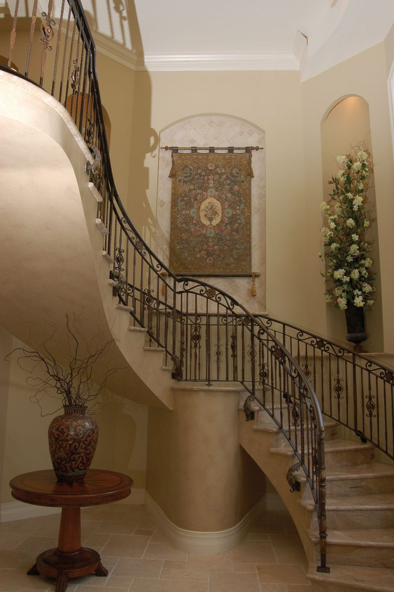The stunning two story foyer has a circular staircase for Two story spiral staircase