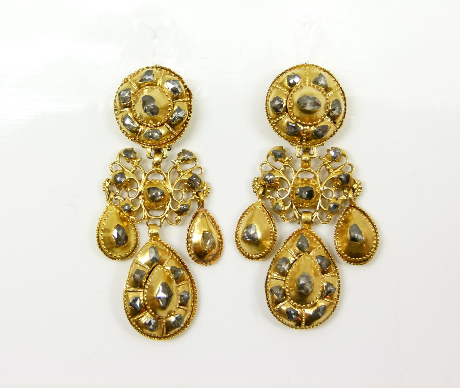 Pair of 17th century rose cut diamond and gold triple drop pendant earrings, Portuguese, c.1680, with graduated stepped cluster drops from a small openwork diamond set cartouche, stepped round cluster tops, all close set in gold