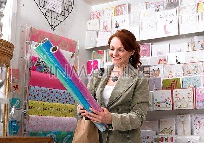 Display Wrapping racks   Young Woman Looking At Wrapping Paper From Display Rack Stock Photos ...