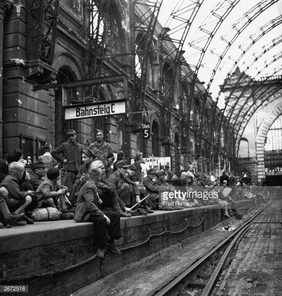 Homeless travellers fill a dilapidated Berlin railway station platform, shortly after Germany's defeat in World War II. They are poorly dressed and many carry small bundles of belongings, amongst them are soldiers who have made their own way from Germany's Russian Front.
