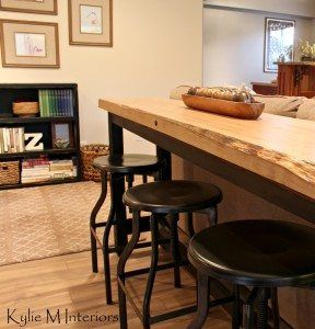 live edge bar table behind sectional with industrial stools in a