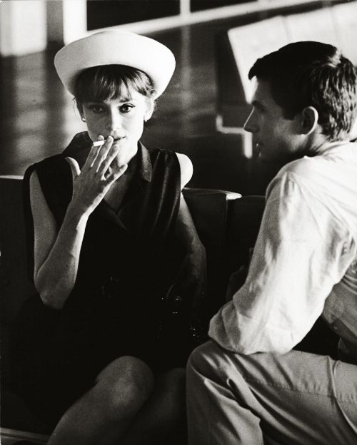 Audrey Hepburn smoking a cigarette while sitting next to the American actor Anthony Perkins. Paris, July 1962. Photo by Pierluigi