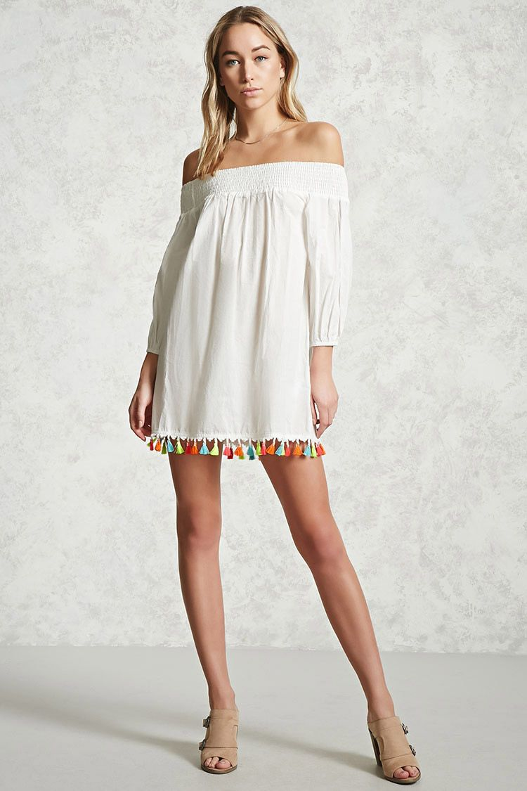 A semi-sheer woven dress featuring a smocked off-the-shoulder neckline, 3/4 sleeves with elasticized cuffs, and a colorful tasseled hem.