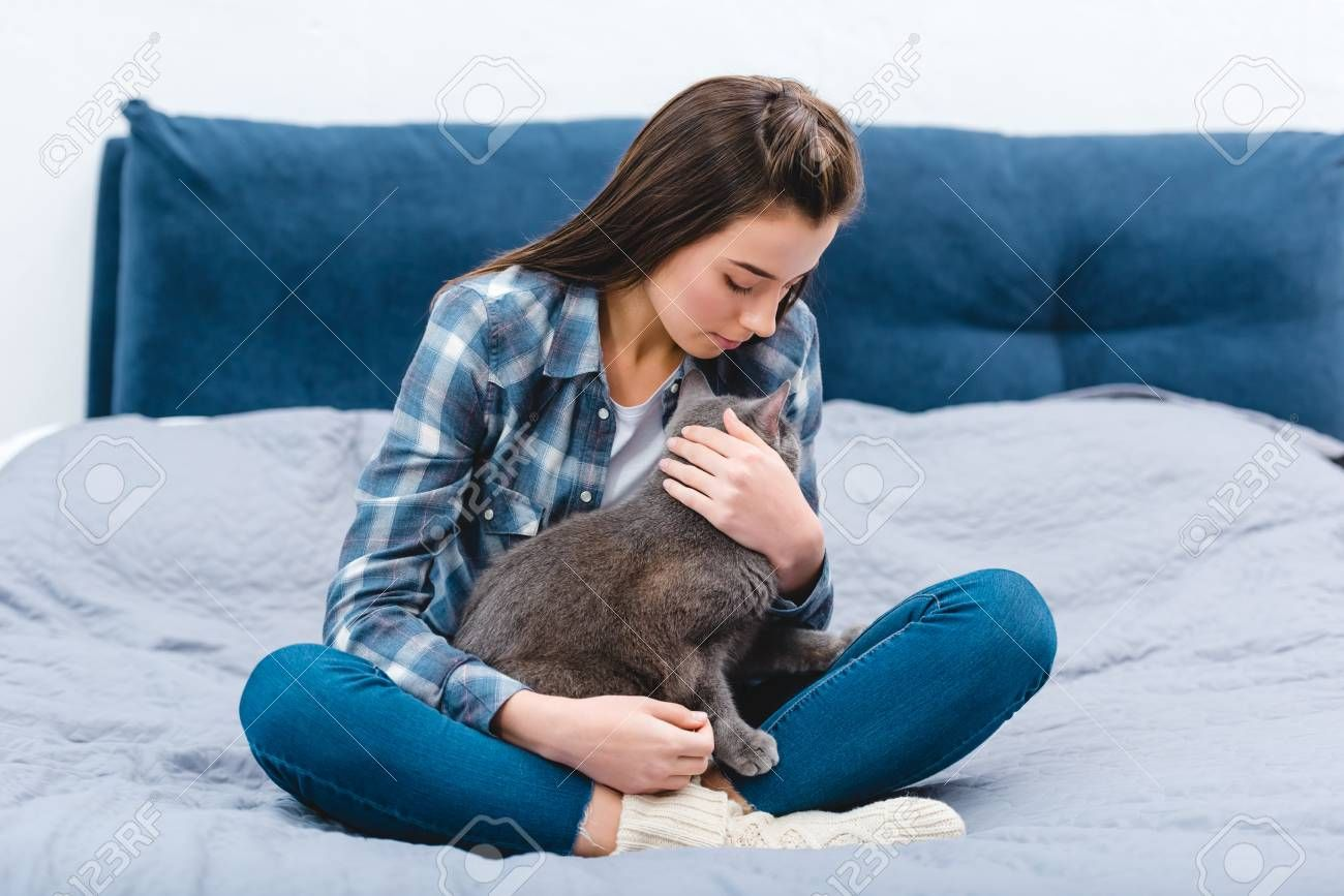 Beautiful Young Woman Sitting On Bed With Cute British Shorthair