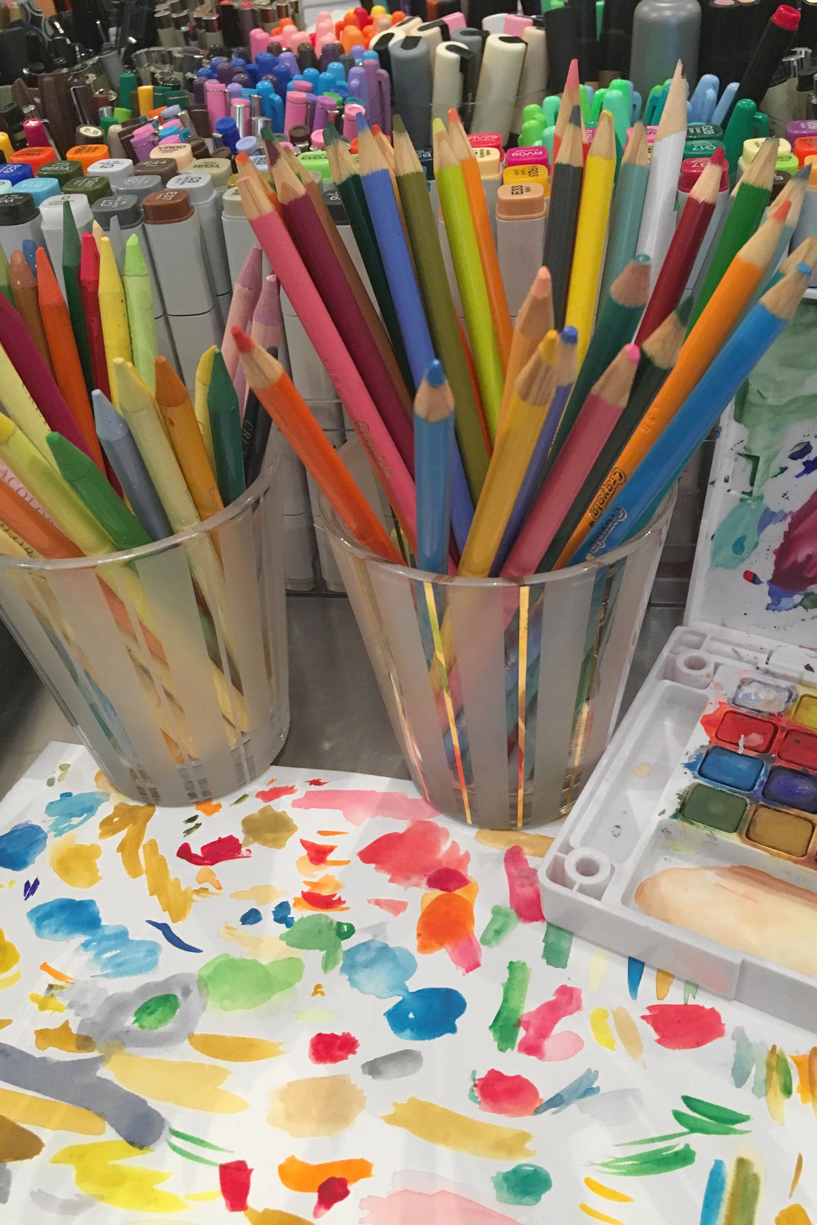 A desk full of rainbow watercolors colored pencils and a