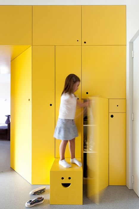 "cool storage wall. ""Just stick your fingers into the smiley face to pull out the stool!"""