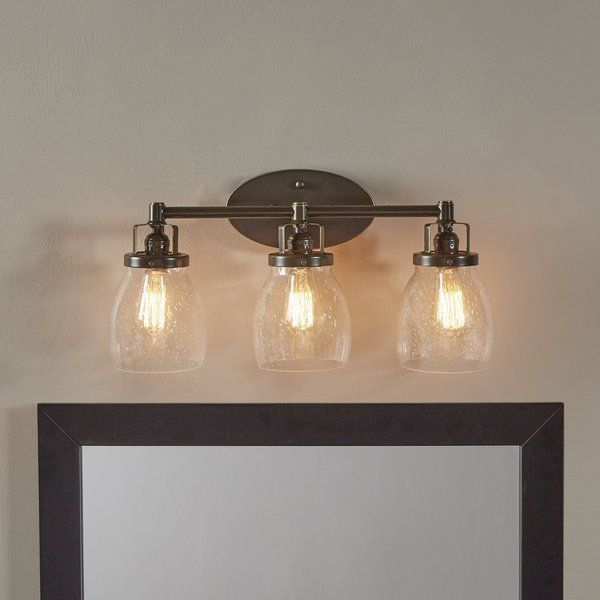 This 3 light vanity fixture in heirloom bronze provides abundant light for your bath vanity while adding a layer of todays style to your interior