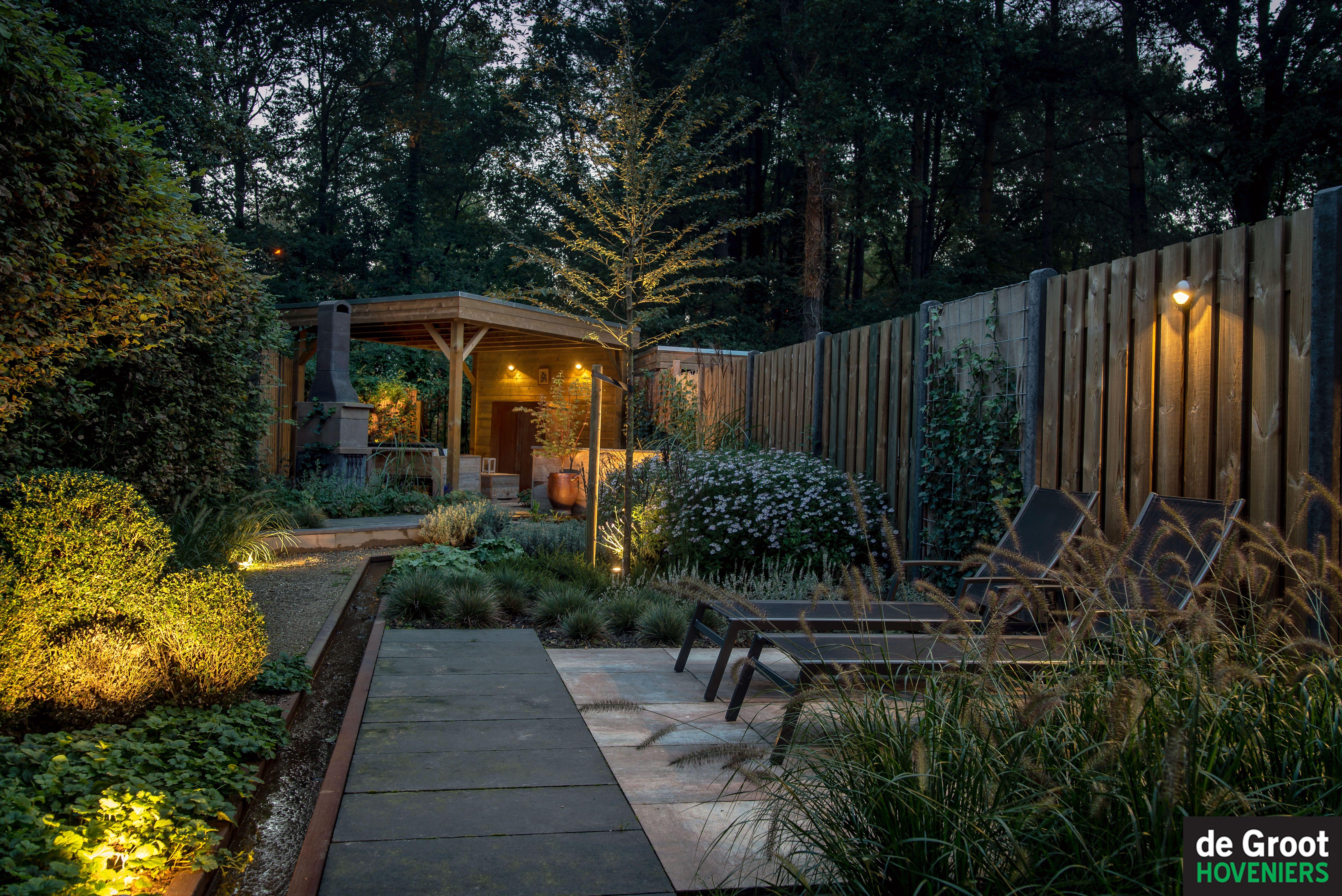 tuin waarin het schemert en de verlichting is ingeschakeld op de schutting en wand van
