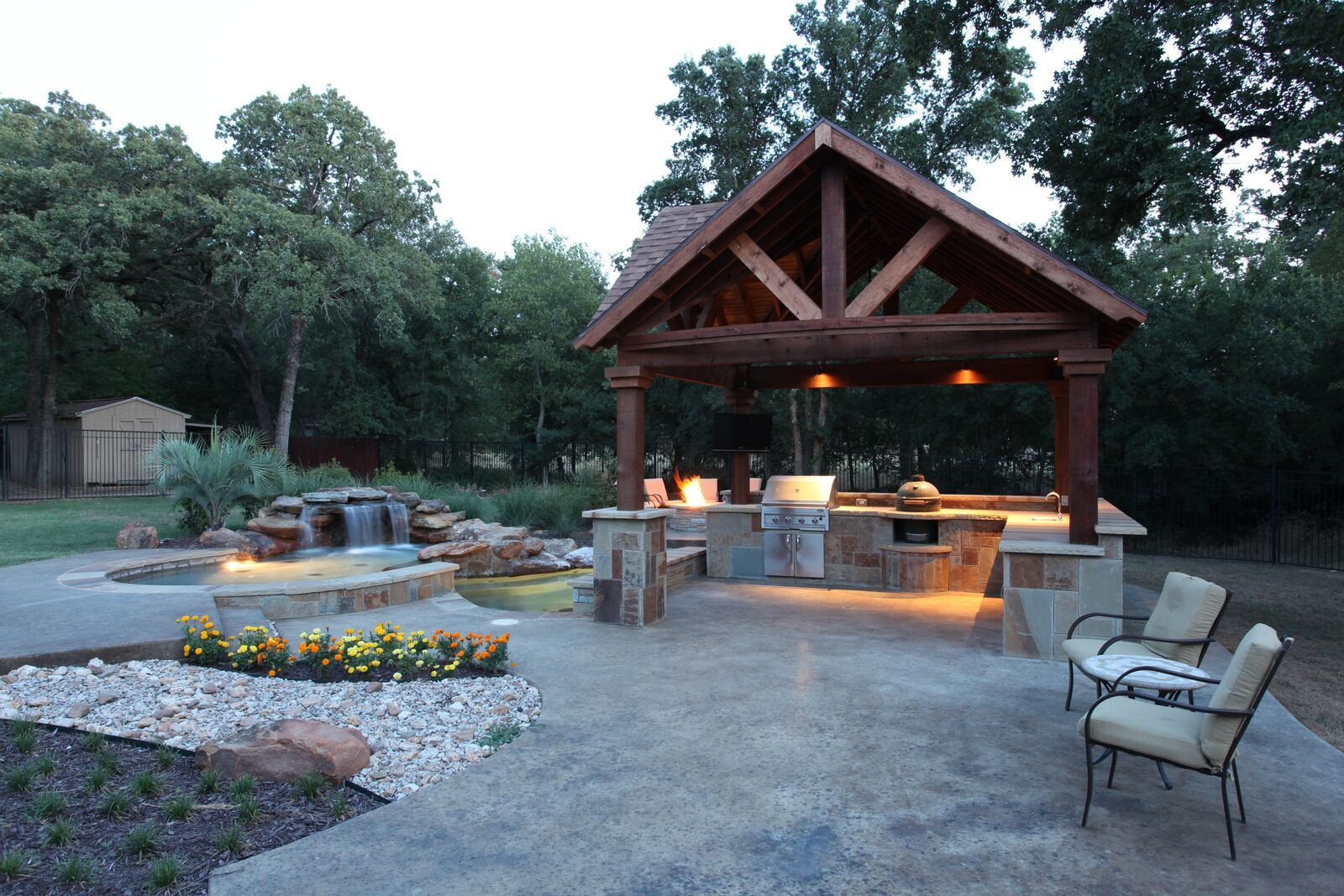 This outdoor kitchen has its own space! Built in a beautiful pavilion, it has all the comforts of an indoor kitchen- BBQ, green egg, and sink with running water. By Outdoor Signature in Argyle, TX