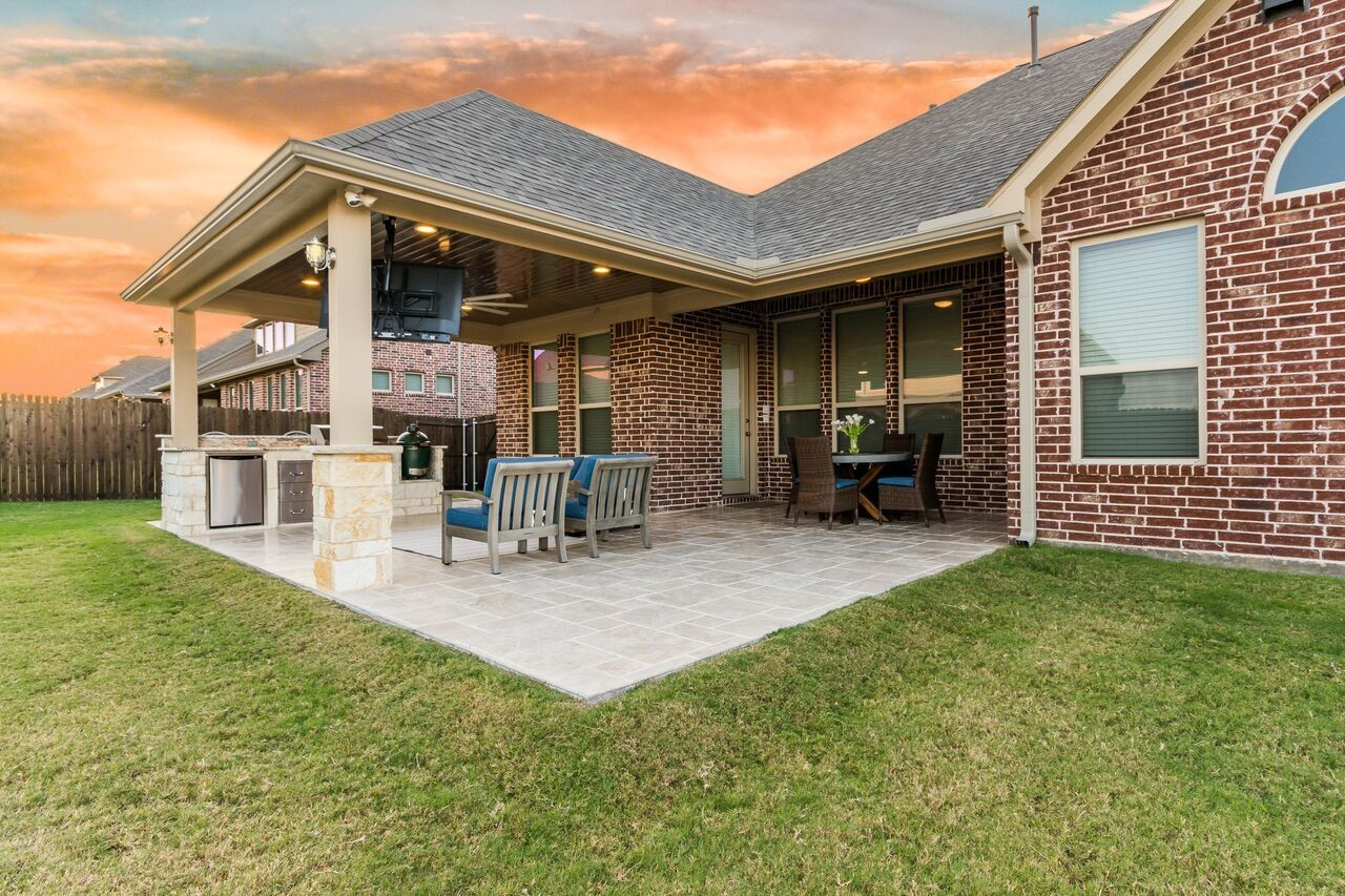 Hip Roof Patio Cover Attached To The House With Outdoor Kitchen And Travertine Tile Flooring Outdoor Remodel Patio Design Patio