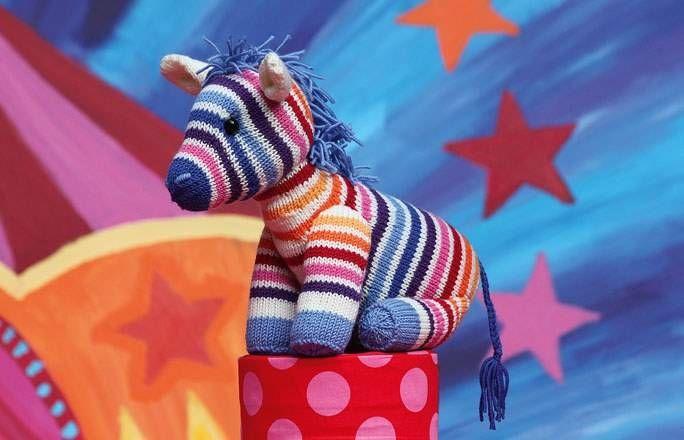 Bild der Frau -  Ist sie nicht süß, die bunte Zebra-Dame Nora? In unserer Anleitung erfahren Sie Schritt für Schritt, wie Sie sich das Regenbogen-Zebra selber stricken können.