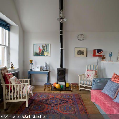 Farbig gemusterte Sofakissen und ein dazu passender Teppich sorgen - wohnzimmer gemutlich kamin