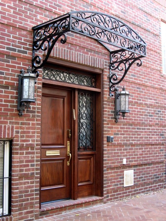 arched glass canopy framed out of steelwrought iron decorated with a graceful and simple scroll work