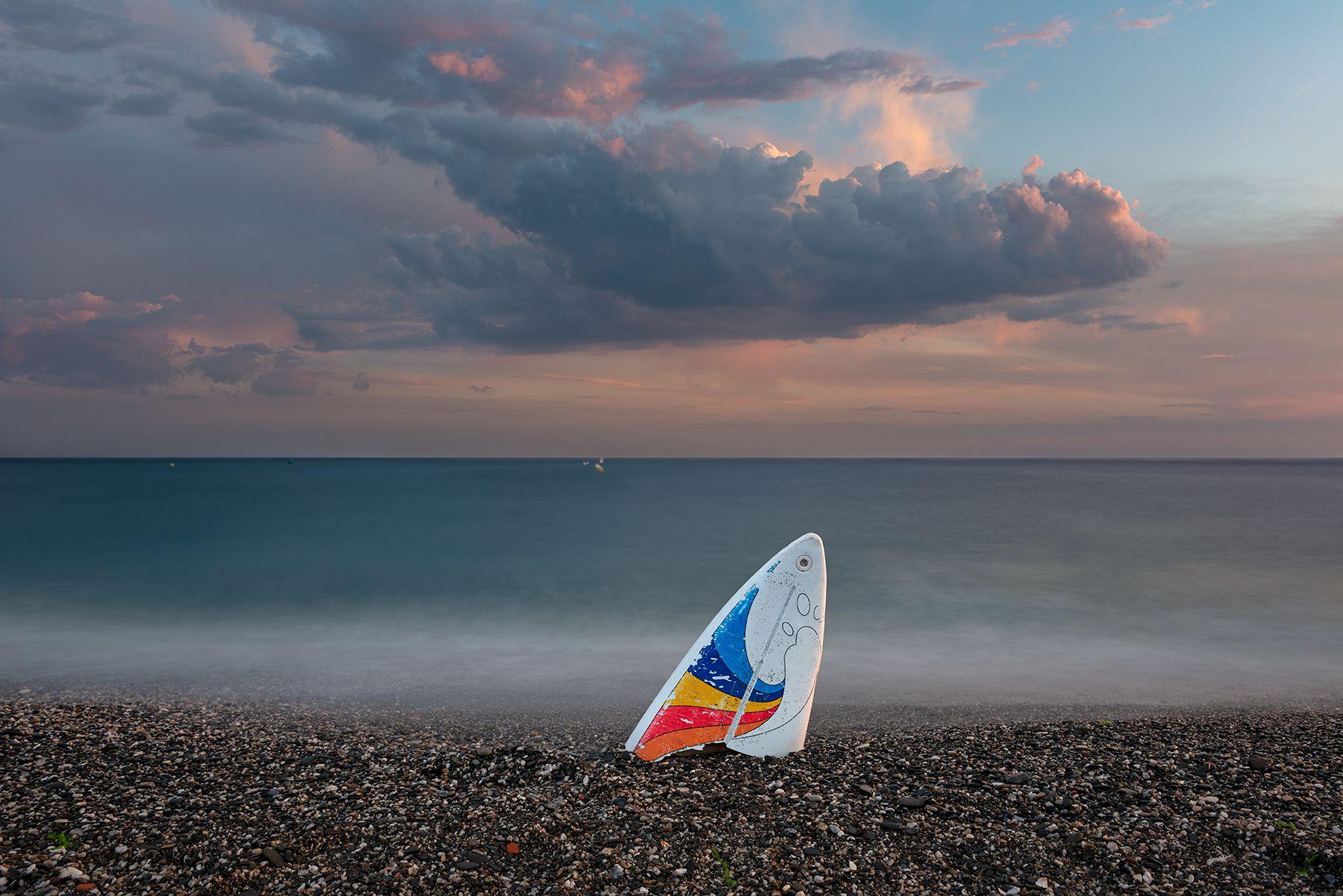 Atardecer con nubes y tabla de surf rota