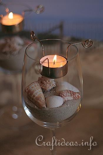 Wine glass, tea candle and seashells centerpiece