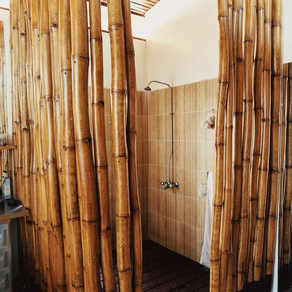 A Ghanian-born architect rediscovered his roots when moving back with his family to Accra. The house he designed includes asix-by-six-foot shower with a cage of bamboo polesaround a hardwood-slatted deck, which allows water to seep into a concrete pan that empties into the main drainage system.  Photo by: Dook