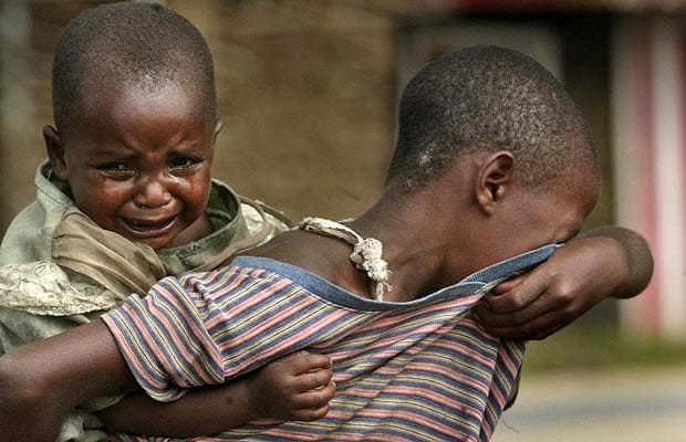 In this November 6 photo, Protegee, carrying her sibling on her back, cries as she looks for her parents in the village of Kiwanja in eastern Congo