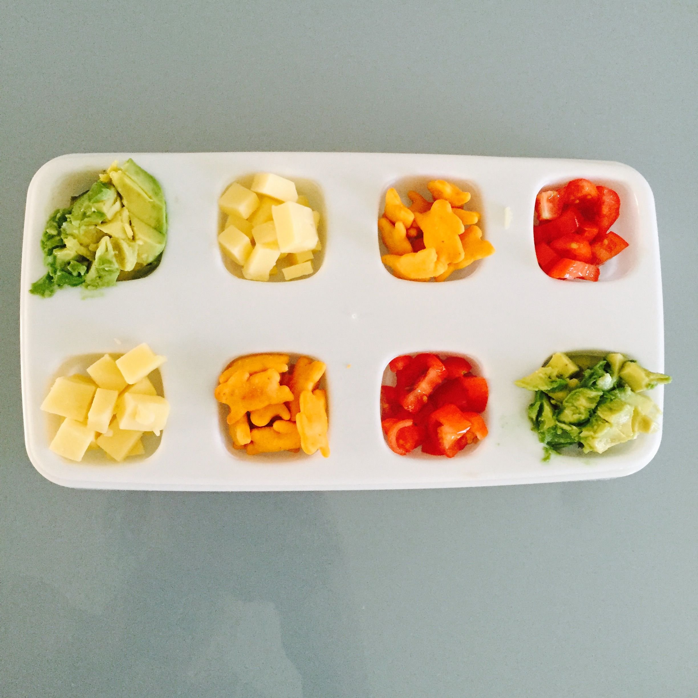 Toddler buffet: chopped avocado, diced tomato, cubed cheddar cheese, bunny crackers