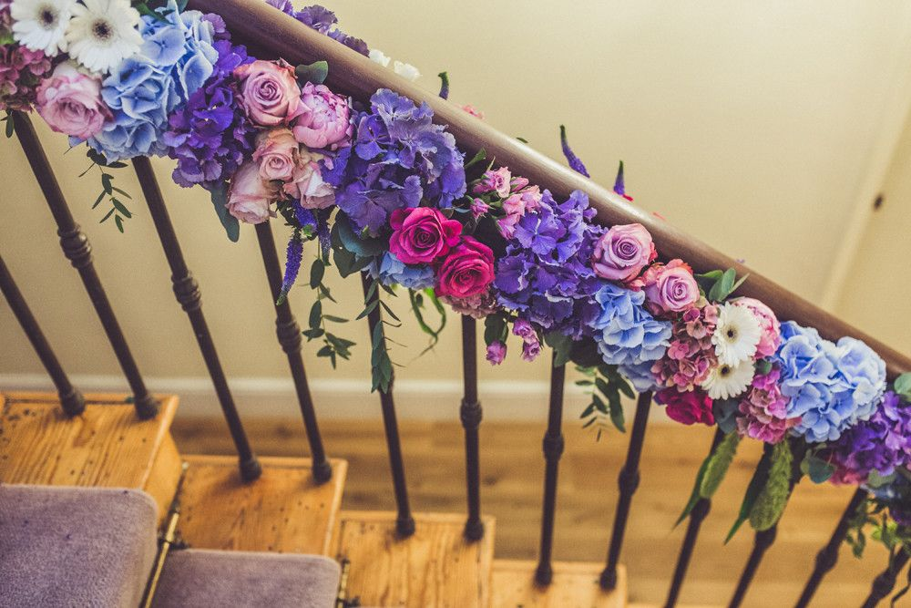Staircase bright flowers including hydrangeas, roses & gerberas - Images by Claire Penn Photography - Jenny Packham wedding dress & Harriet Wilde shoes for a classic wedding with bright florals & Coast pastel bridesmaids dresses. Groom wears Marc Wallace suit.