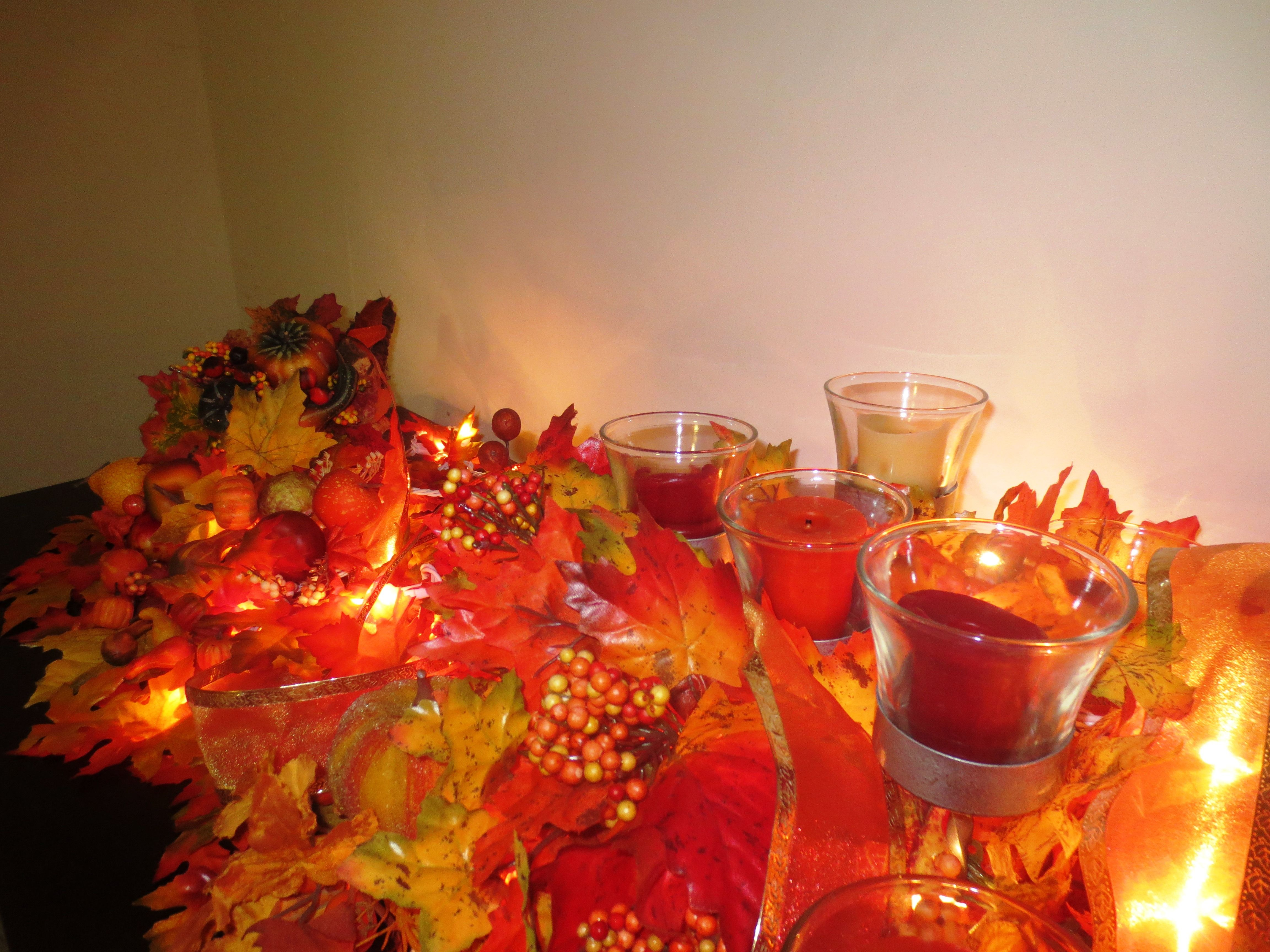 Thanksgiving - The traditional symbol of this holiday is the cornucopia.  I placed one with some silk leaves and autumn fruit and vegetables.  The mass of leaves is several autumn swags with some orange organza ribbon.  The candle colors are orange, red, and yellow.  I just added things that reminds me a the plenitude of the season.