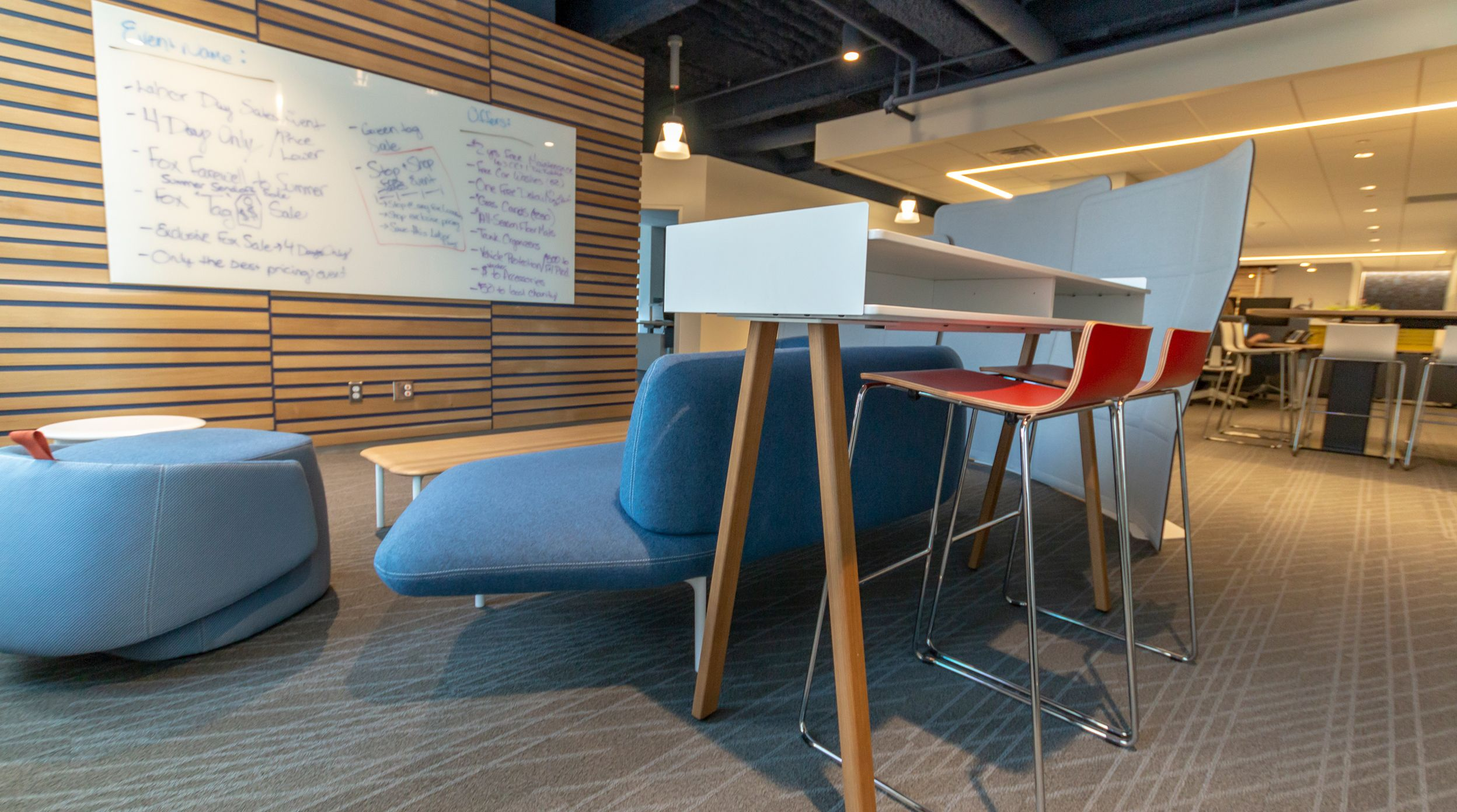 Via Design Provides An Interior Update To Fox Motors Corporate Office In Grand Rapids Michigan Wood Paneling Lounge Area Blue Chair Ottoman