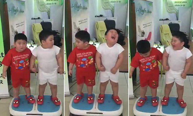 Twins giggle on vibrating exercise machine as they're shaken up