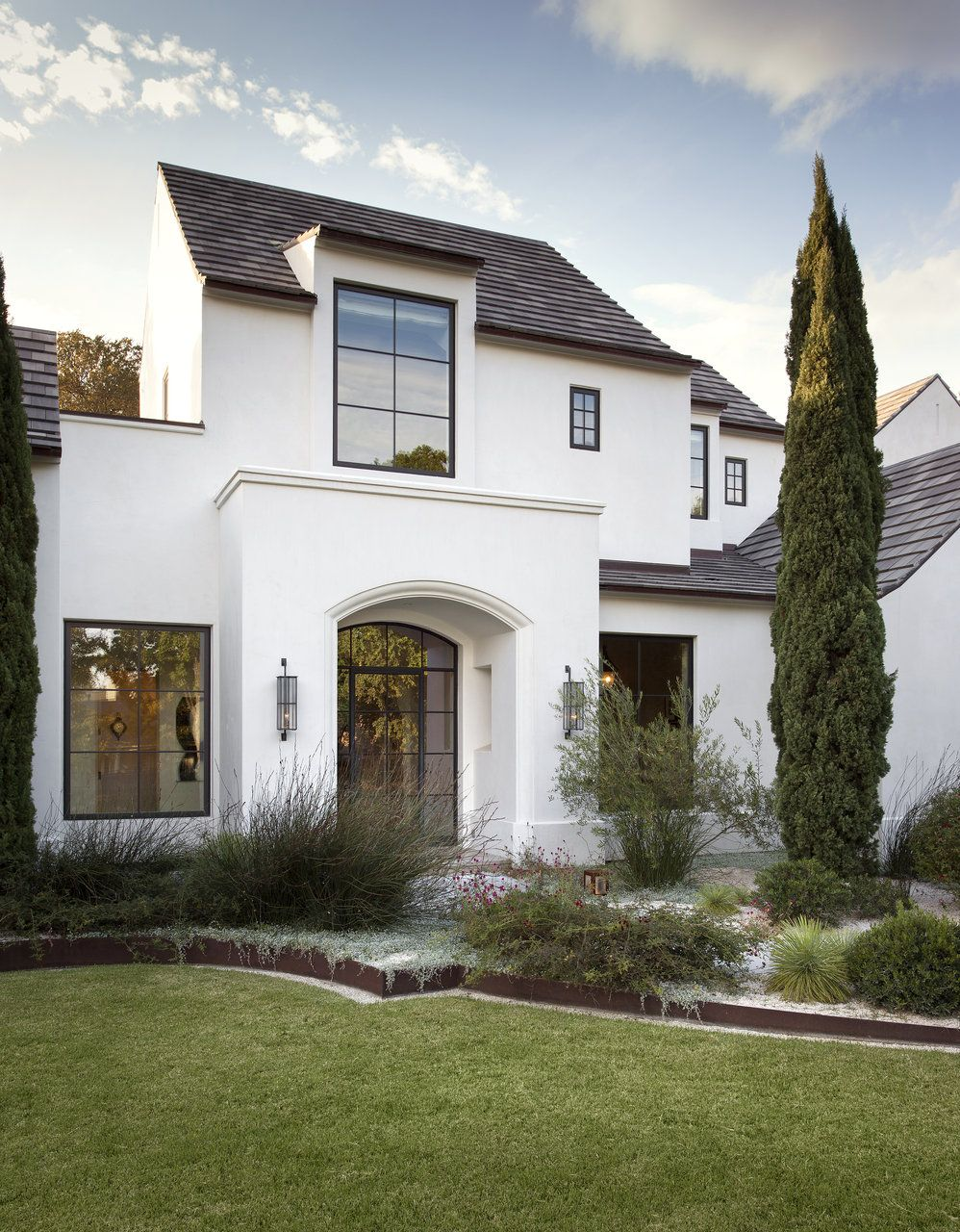White exterior with black window frames via ryan street associates white stucco house