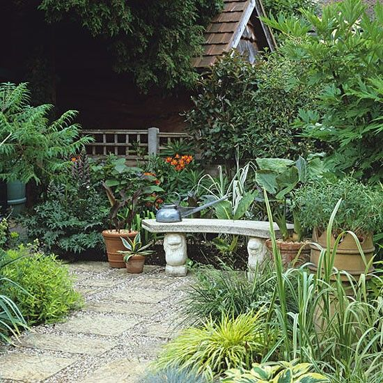 An inviting stone bench in a small courtyard of paving for Courtyard landscaping ideas