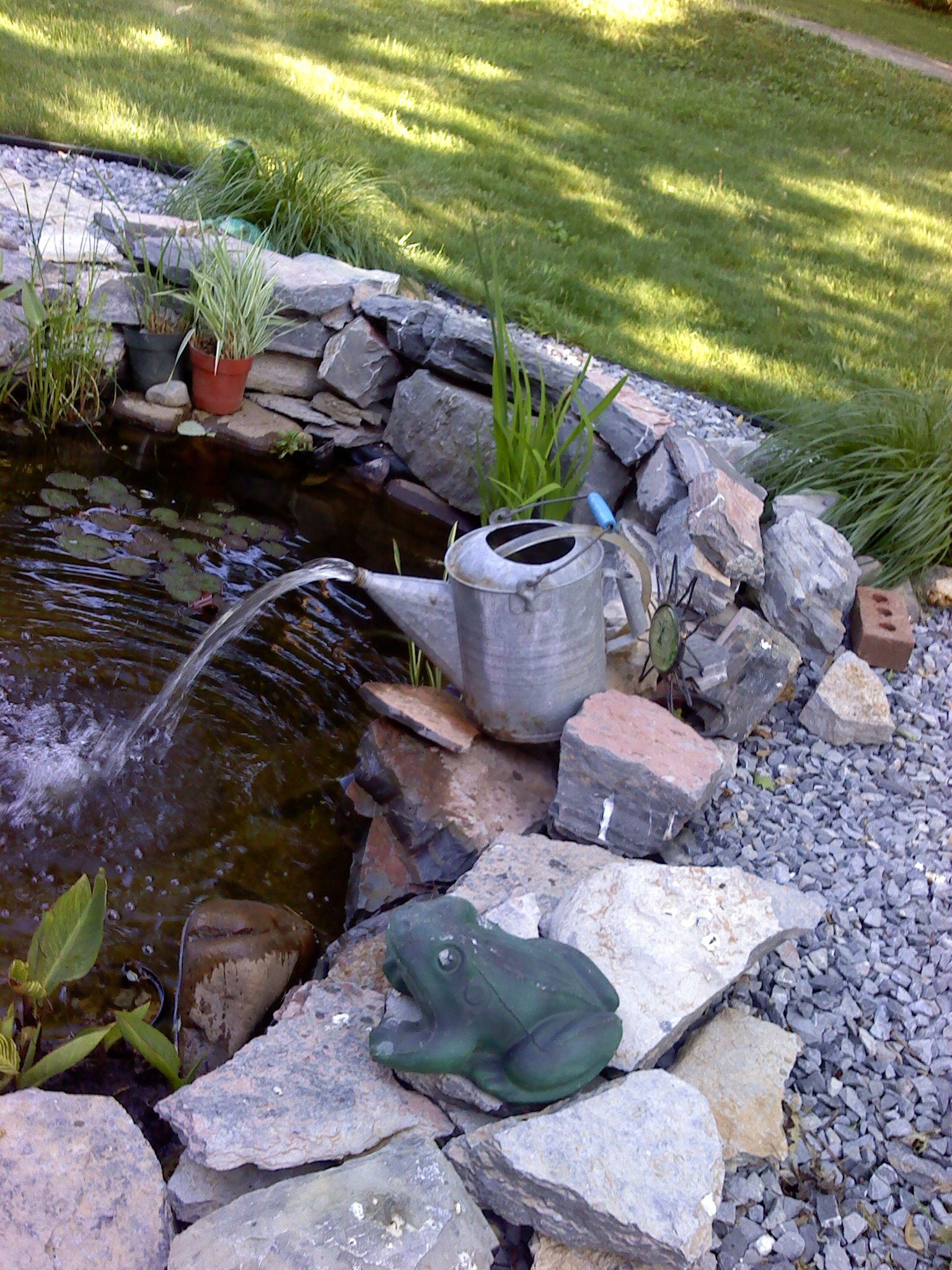 Our fish pond with watering can fountain for my garden for Garden pond water features