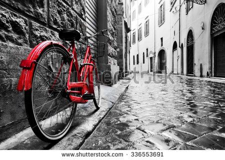 Retro vintage red bike on cobblestone street in the old town. Color in black and white. Old charming bicycle concept. - stock photo