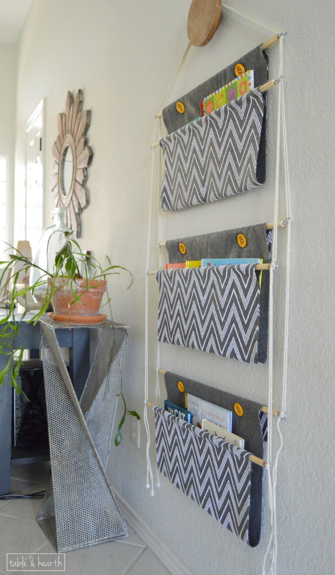 an easy, customizable way to store children's books?? This easy holder only uses rope, wood dowels, and some fabric and can be hung anywhere!