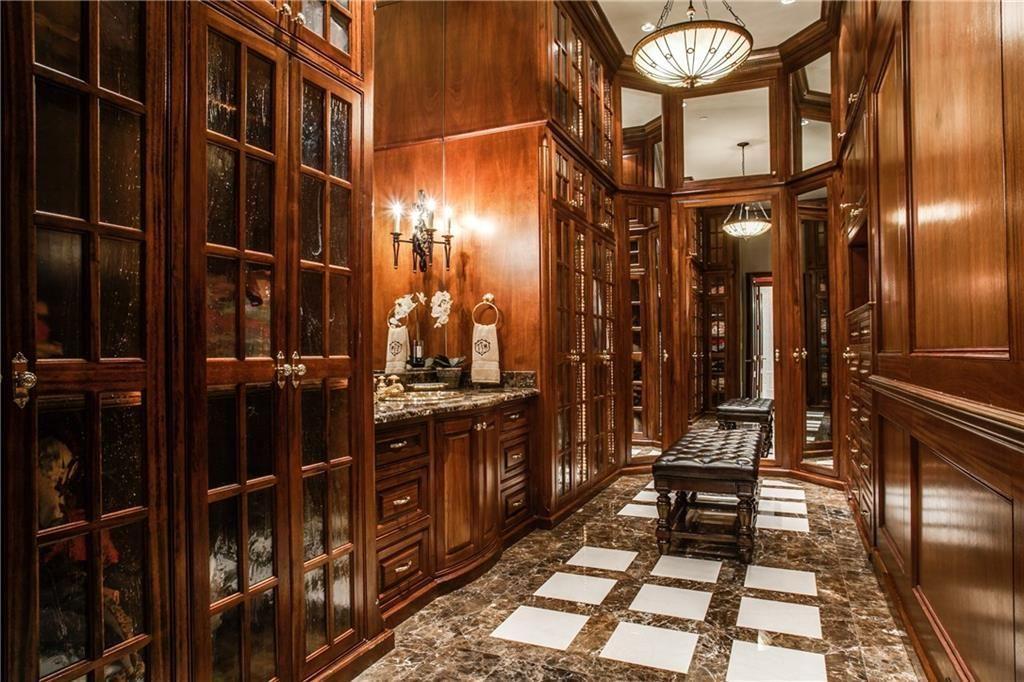 Luxury Custom Closets craftsman closet with soapstone tile floors, crown molding, built