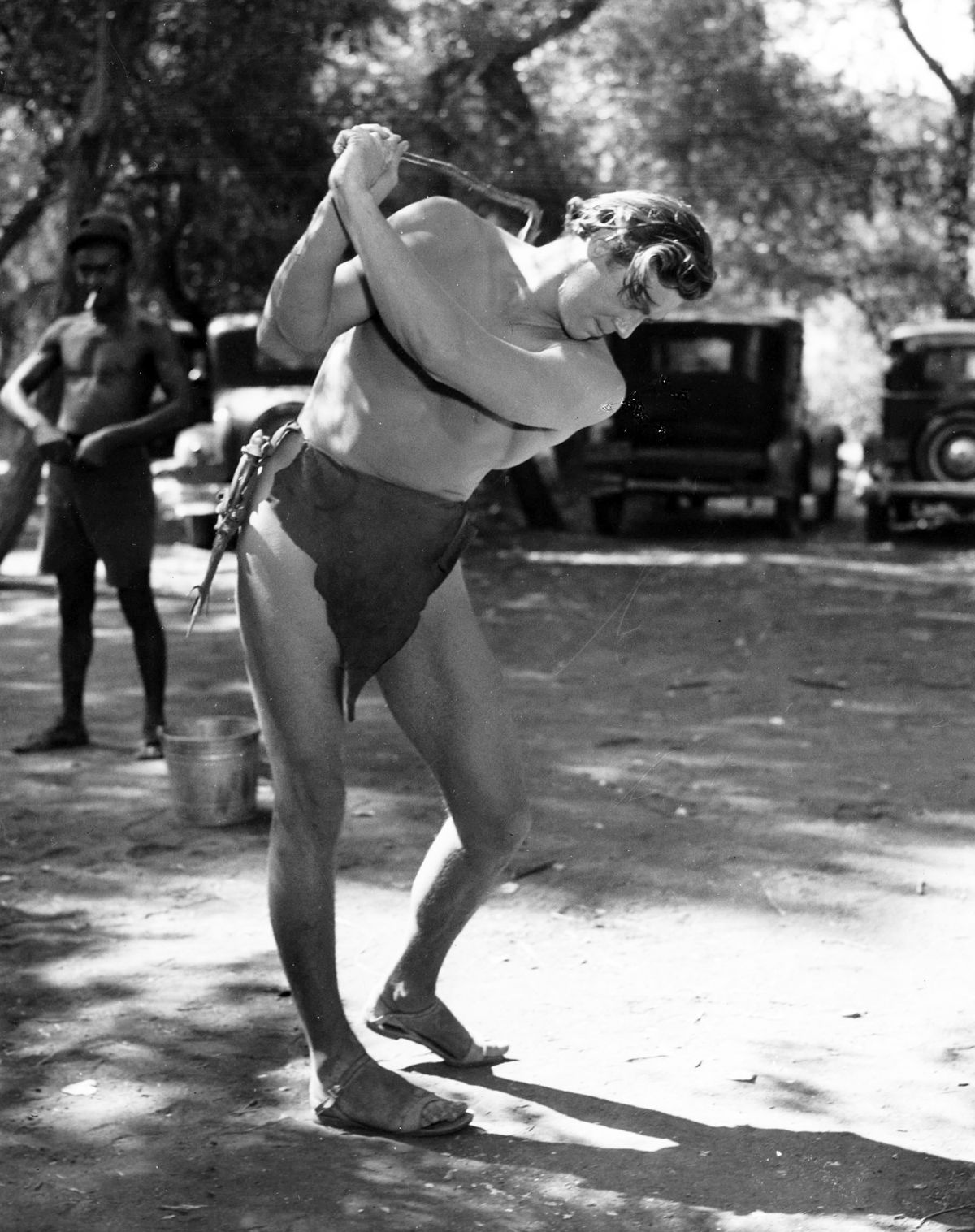 Johnny Weissmuller practices his golf swing between takes while on location.