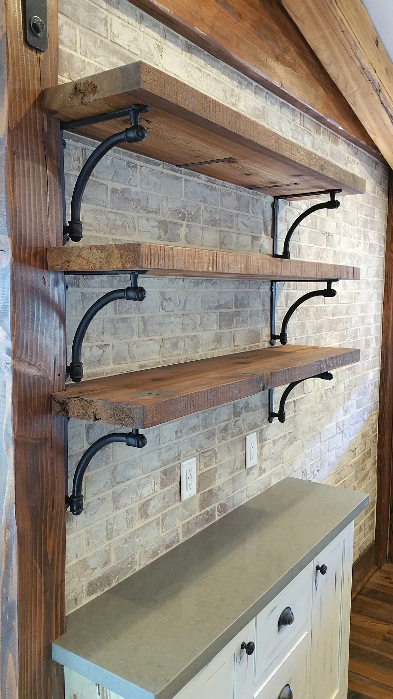 open shelves with cast iron brackets on newly installed brick wall a fresh