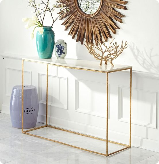 sleek gold leaf and marble console table with a slim open frame design from wisteria