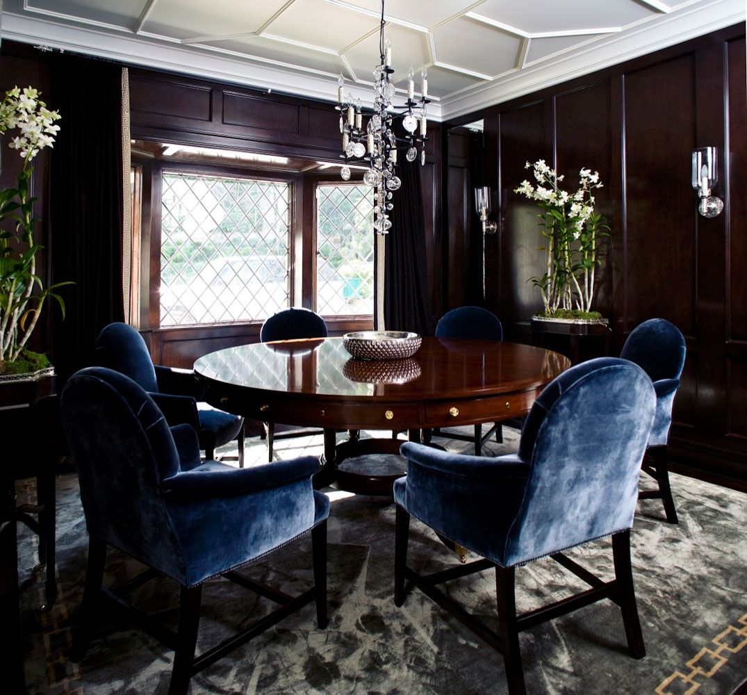 Dining Room With White Coffered Ceiling Dark Paneled Walls Blue Velvet Armchairs Around A