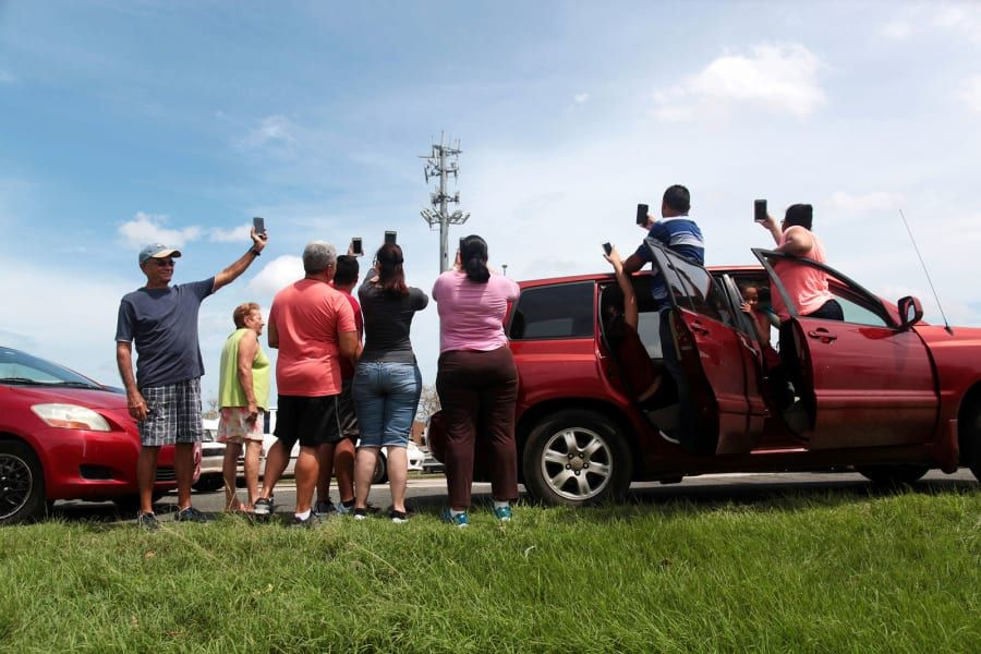 People stop on a highway near a mobile phone antenna tower to check for a signal in Dorado, Puerto Rico, on Sept. 22.