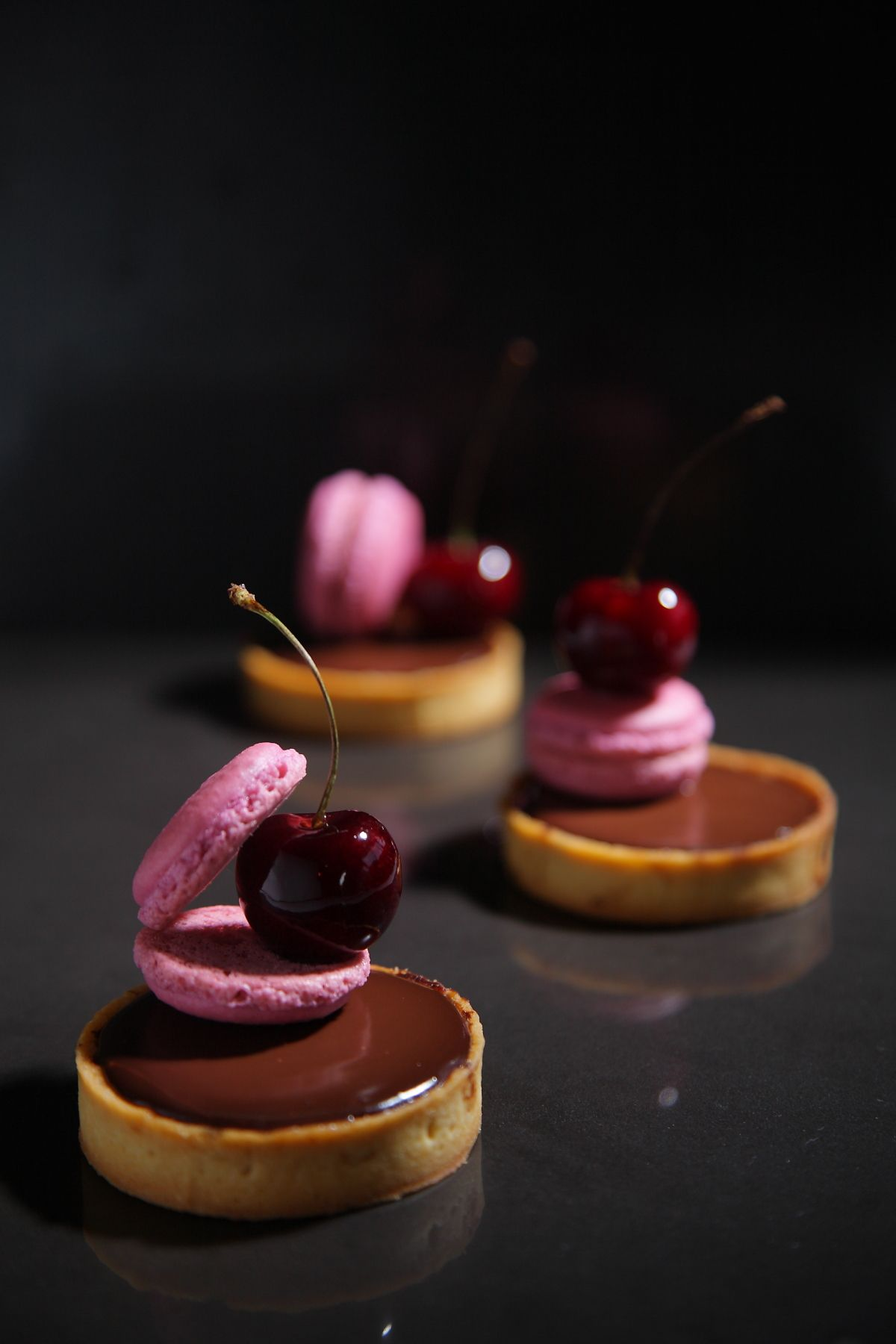 No description so w/ my culinary instincts, I'd say this is a dark chocolate tartlet w/ bing cherry macaroons, maybe flavored with hazelnuts, spiked with some kind of nut or flavored liquer